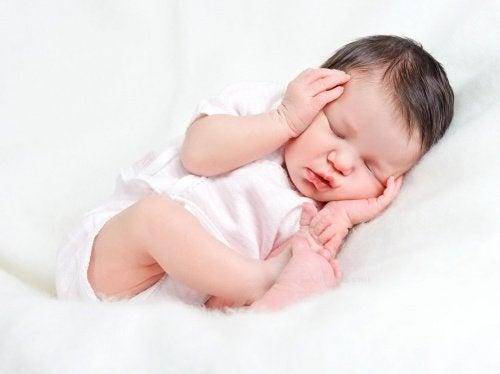 頭を抱えて眠る赤ちゃん