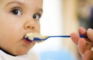 青いスプーンで食べさせてもらう赤ちゃん