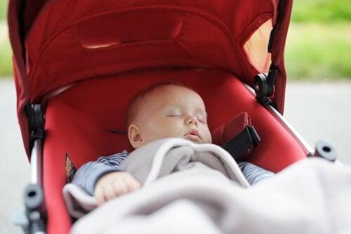 赤いベビーカーで眠る赤ちゃん