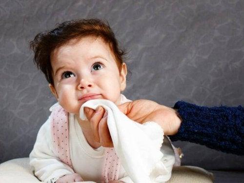 赤ちゃんのあごをガーゼで拭く親