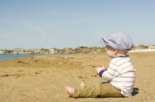 ビーチに座って海を見る赤ちゃん