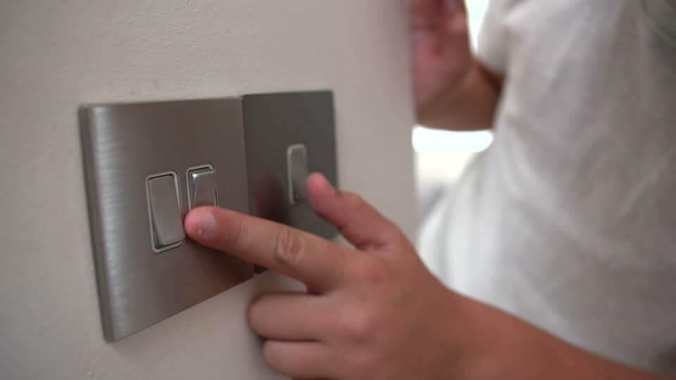 電気のスイッチを入れる子供