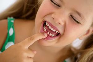 歯が抜けた跡を示す女の子