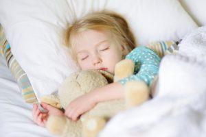 クマのぬいぐるみと昼寝する女の子