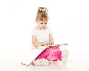 本を見ながらおまるに座る女の子