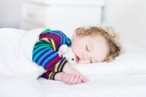 カラフルな服で昼寝をする男の子