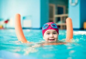 プールで浮き棒を使う子供