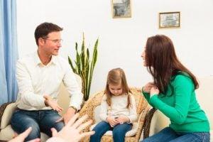子供をはさんでケンカする両親