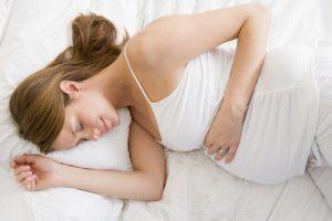 ベッドで眠る妊婦