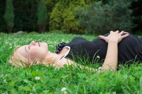 芝生に横たわる妊婦
