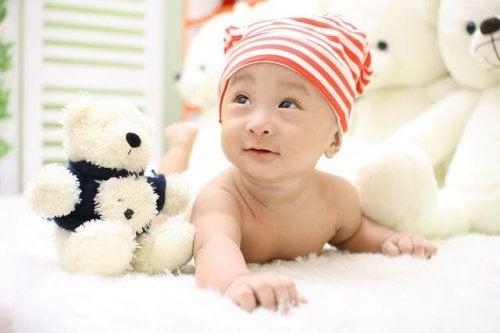 白いぬいぐるみに囲まれている赤ちゃん
