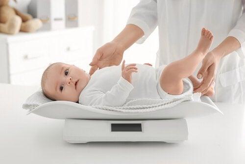 小児科で体重計に乗せられる赤ちゃん