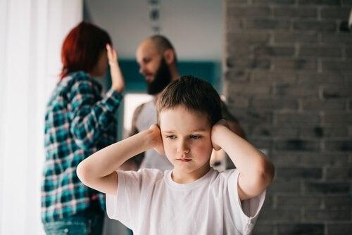 親の口論に耳をふさぐ男の子