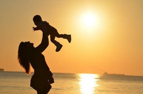 夕焼けの海で子供を抱き上げる母親