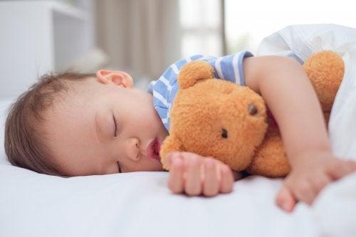 くまのぬいぐるみと寝る男の子