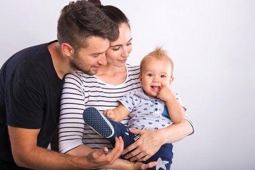 赤ちゃんを抱くママと寄り添うパパ