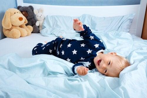 ベッドで遊んでいる赤ちゃん 一人で寝かせる